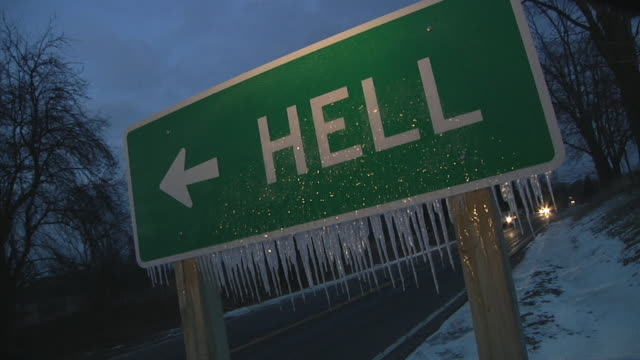 cu road sign with icicles pointing to 'hell' at night / cars pass by / chelsea, michigan - ewigkeit stock-videos und b-roll-filmmaterial