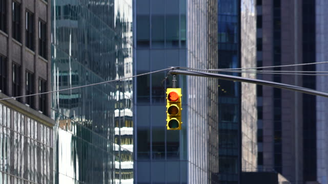 vídeos de stock e filmes b-roll de road signal stands at front of rows of high-rise office buildings along the avenue at midtown manhattan new york ny usa on apr 22 2018. - sinal rodoviário