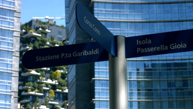 road signs and skyscrapers in gae aulenti square in milan - segnaletica stradale video stock e b–roll