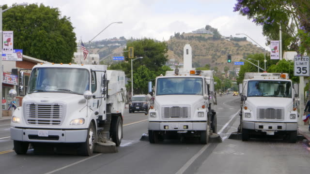 Road sweeper street cleaning machines perform cleaaning and maintenance in Los Angeles, California, 4K