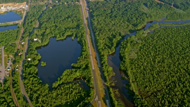 AERIAL Road through the countryside surrounded by a river and lake