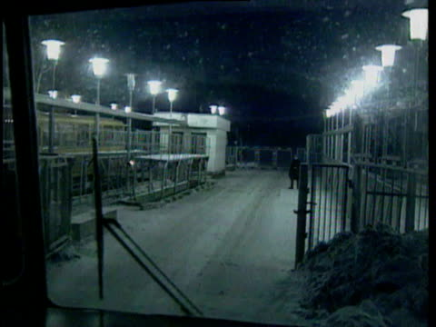 road to chelyabinsk 65 and checkpoint gate; barbed wire fence; snow, winter; buildings in town ; well-to-do looking people in street, women wearing... - russia点の映像素材/bロール