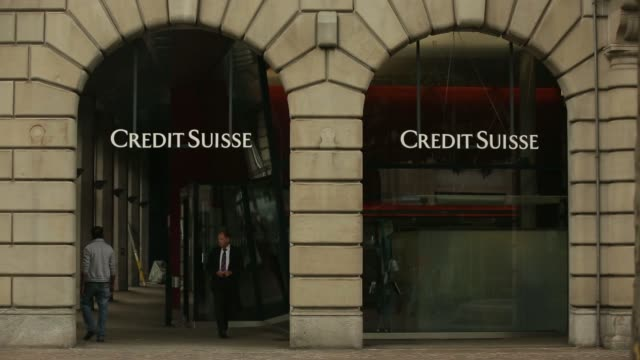road traffic and pedestrians pass a credit suisse group ag bank branch in zurich switzerland on monday july 21 pedestrians walk past a branch of... - banking sign stock videos and b-roll footage