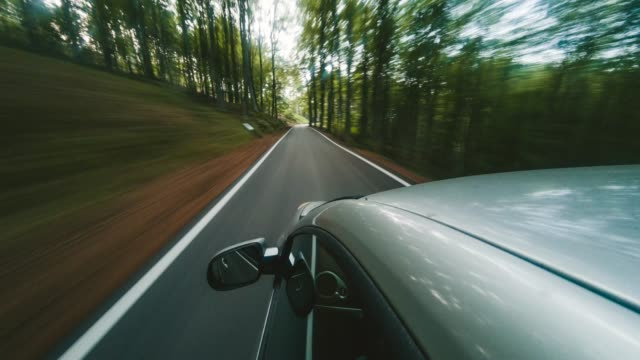 road trip in the middle of the forest. timelapse video - sports car stock videos & royalty-free footage