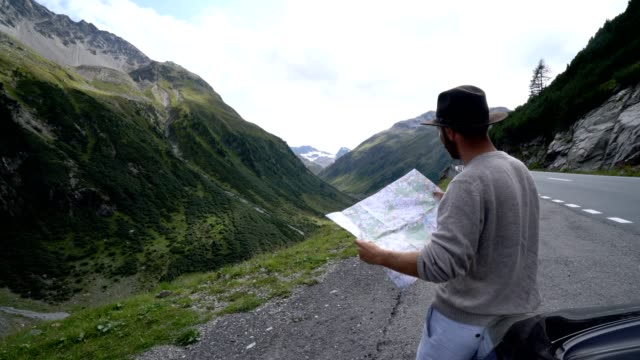 road trip, man checking map on mountain pass, switzerland - road map stock videos & royalty-free footage