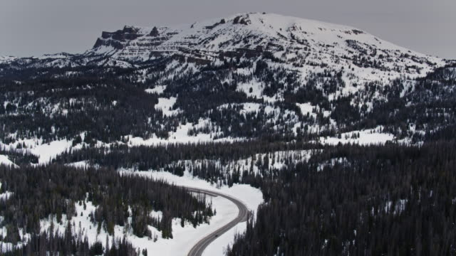 road winding through snow covered forest in wyoming - aerial - grand teton stock videos & royalty-free footage
