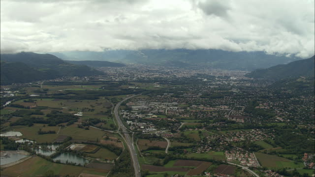 aerial ws road winding through valley along cityscape / grenoble, france - grenoble stock-videos und b-roll-filmmaterial