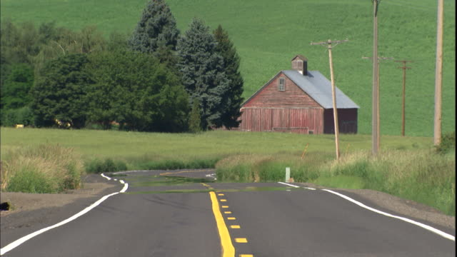 a road winds past a barn in the green countryside. - palouse stock videos & royalty-free footage