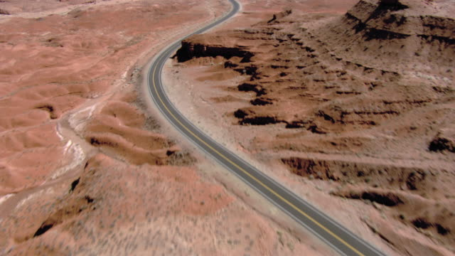a road winds through the desert around bluffs. - empty road stock videos and b-roll footage