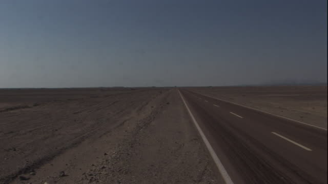 A road with a dotted white line down the middle stretches across a desert.