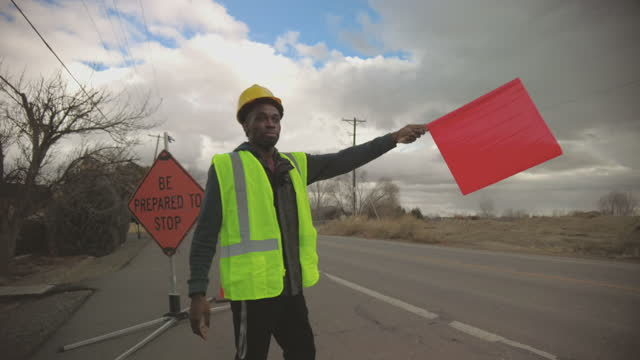 road work zone flag man black african male road construction and traffic flow worker 4k video series - construction vehicle stock videos & royalty-free footage