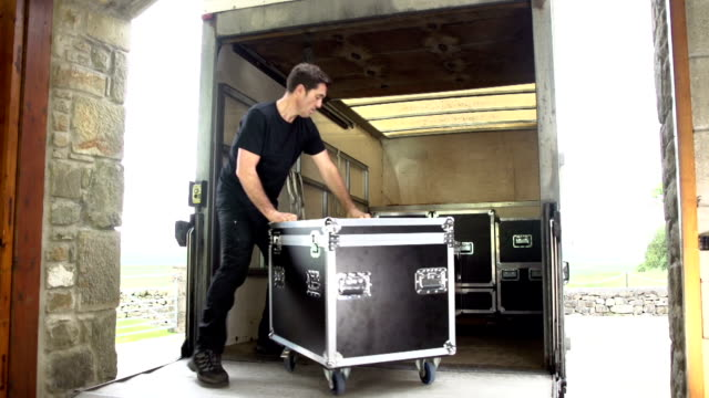 roadie loads truck with flightcase and sound equipment - flight case stock videos and b-roll footage