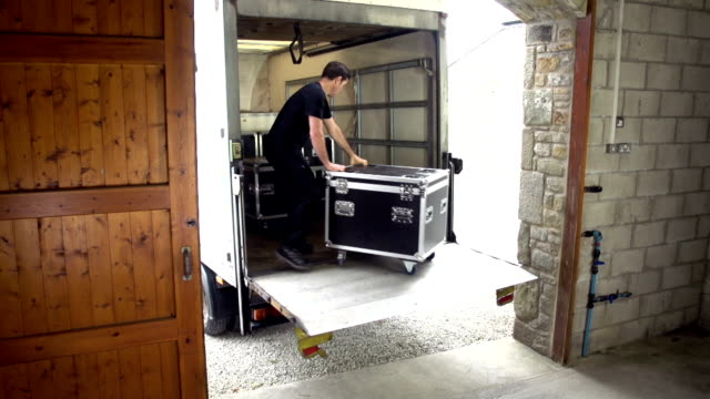 roadie loads truck with flightcases and sound system - flight case stock videos and b-roll footage