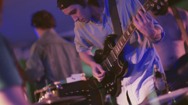 roadies prepare outdoor stage for concert as young guitarist adjusts levels on his amp - crew stock videos & royalty-free footage