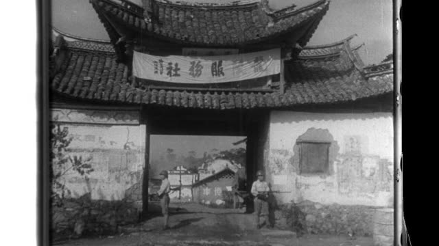 A roadside notice is posted near the empty town of Yuengching Imperial Japanese Army soldiers guard the city gate of Longling where enemy supplies...