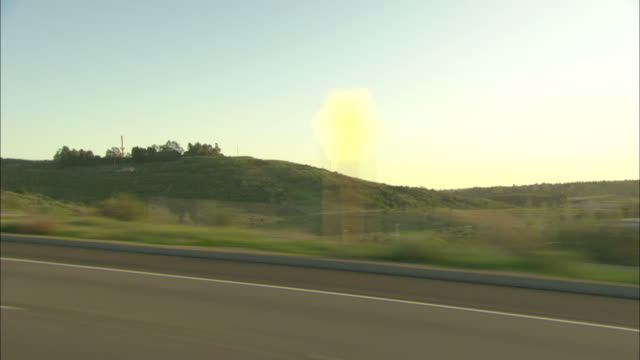 roadside signs and hills blur as they pass. - roadside stock videos & royalty-free footage
