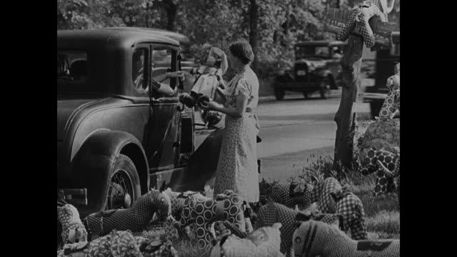 roadside yard sale w/ many stuffed fabric animals standing outside fg woman standing by parked car window holding up handmade dressed toy monkey for... - 1937 stock videos and b-roll footage