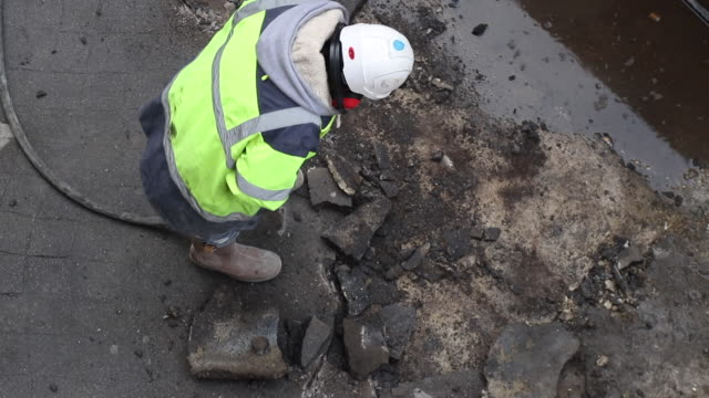 roadworks. overhead view worker with a hammer sting breaks tar - pneumatic drill stock videos & royalty-free footage
