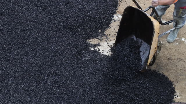 roadworks. tar poured from a wheelbarrow on the road and spread - baustelle stock-videos und b-roll-filmmaterial