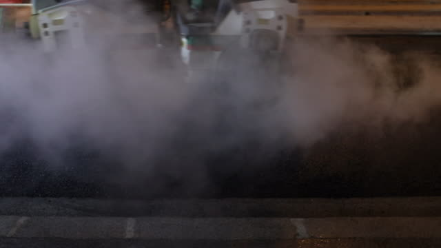 roadworks. to asphalt a road. steamroller flattens the tar, smoke of water vapor - steamroller stock videos and b-roll footage