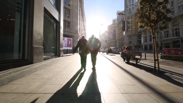 vídeos de stock, filmes e b-roll de roaming shot in early morning sunshine on calle gran via, madrid, spain, europe - de braços dados