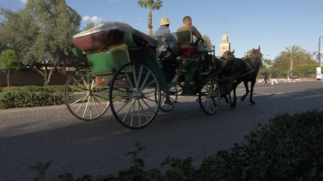 roaming shot of horse and carriage and koutoubia minaret visible in background, marrakech, morocco, north africa, africa - circa 12th century stock videos & royalty-free footage