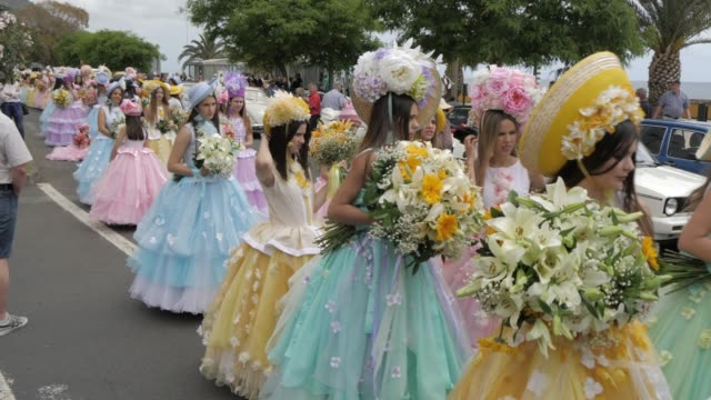 vídeos de stock, filmes e b-roll de roaming shot of pastel coloured flower girls parade at spring festival, funchal, madeira, portugal, europe - dama de honra