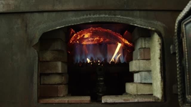 a roaring hot fire underneath a rum distillery still - distillery still stock videos & royalty-free footage