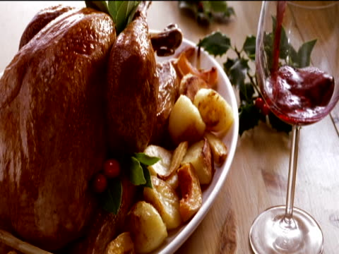 roast turkey and potatoes next to a glass filled with red wine (file size: 257mb) - roast turkey stock videos & royalty-free footage