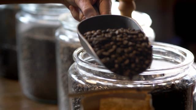Roasted coffee beans being scooped into a bag.