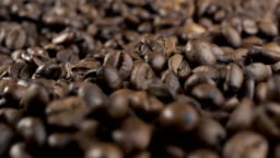 Roasted coffee beans falling down. Slow motion. Close-up shot