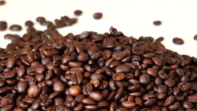 roasted coffee beans falling on top of a stack of the same grain - coffee drink stock videos & royalty-free footage