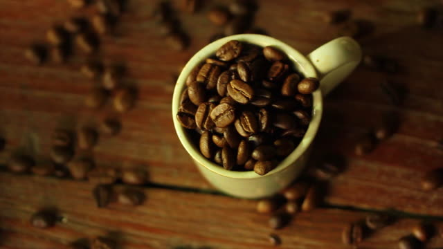 roasted coffee beans on wooden table with sunlight - coffee table stock videos & royalty-free footage