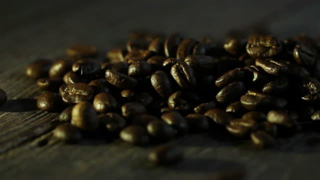 vídeos de stock, filmes e b-roll de grãos de café torrado na textura de madeira - molécula de cafeína