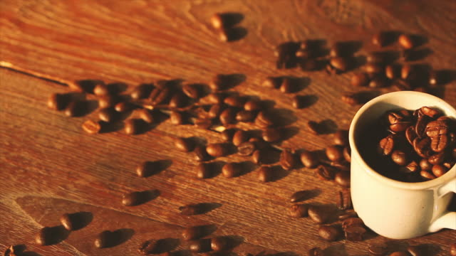roasted coffee beans with coffee cup on wooden table with sunlight - coffee table stock videos & royalty-free footage