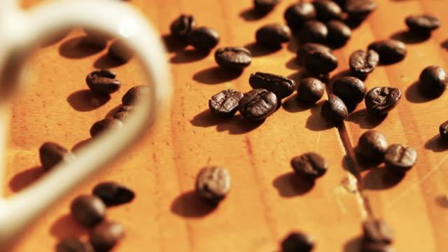 vídeos de stock, filmes e b-roll de grãos de café torrado com xícara de café branca na textura de madeira na luz da manhã - molécula de cafeína