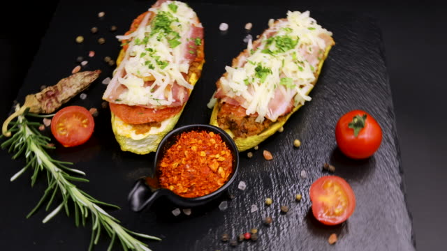 roasted stuffed zucchini with the addition of bacon, tomatoes, mozzarella cheese on the rotating stand - mozzarella stock videos & royalty-free footage