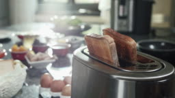 Roasted toast bread popping up from toaster slow motion