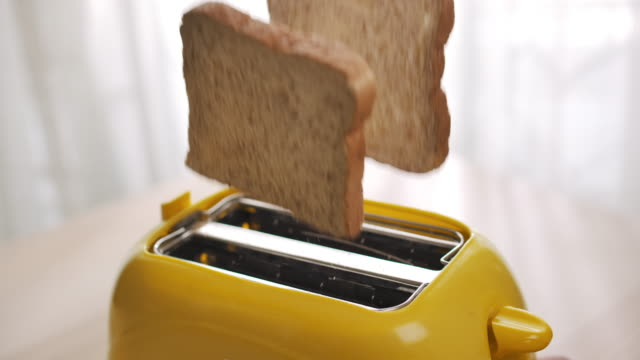 roasted toast bread popping up from toaster,slow motion - toaster appliance stock videos & royalty-free footage