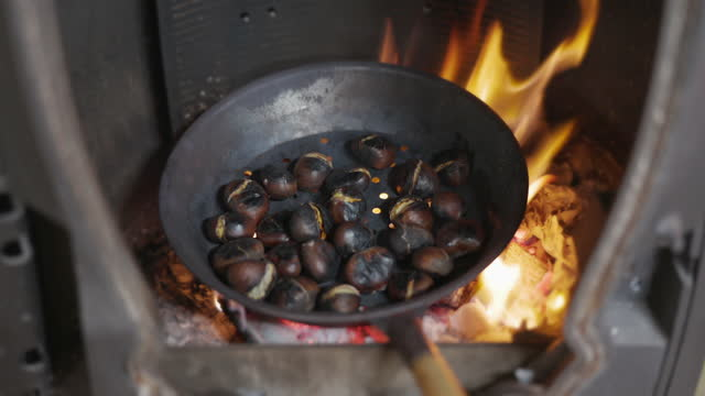 roasting chestnuts in cast iron pan on open fire - roasted stock videos & royalty-free footage