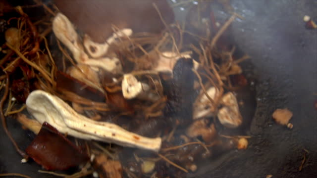 roasting medicinal plants with a spatula - dried food stock videos & royalty-free footage