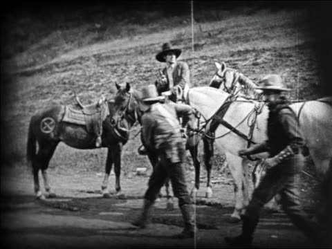 b/w 1924 2 robbers ducking behind horses where other cowboy waits / feature - pflanzenfressend stock-videos und b-roll-filmmaterial