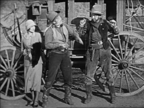 vidéos et rushes de b/w 1924 2 robbers walking away from woman after stagecoach hold-up / feature - 1924