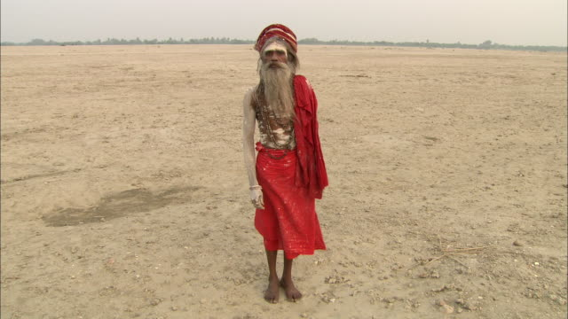 a robed and turbaned holy man stands on a sandy beach in india. - 頭飾り点の映像素材/bロール