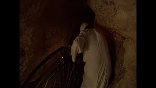 robed egyptian men descend a spiral staircase in a cave. - spiral staircase stock videos & royalty-free footage