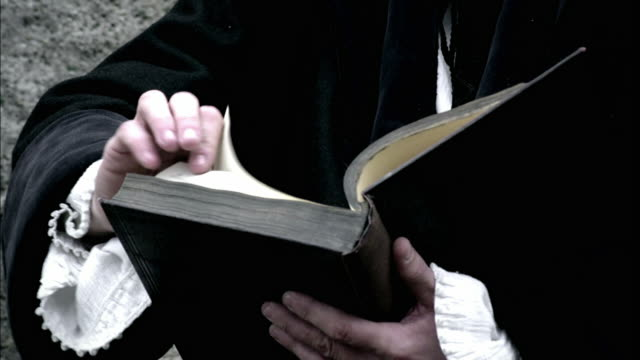 a robed man flips through a book and looks around thoughtfully. - historical reenactment stock videos & royalty-free footage