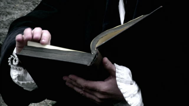 A robed man flips through a book.
