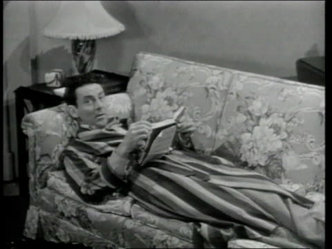 1948 MONTAGE Robed man gets up off couch and shows off features of new, prefabricated home