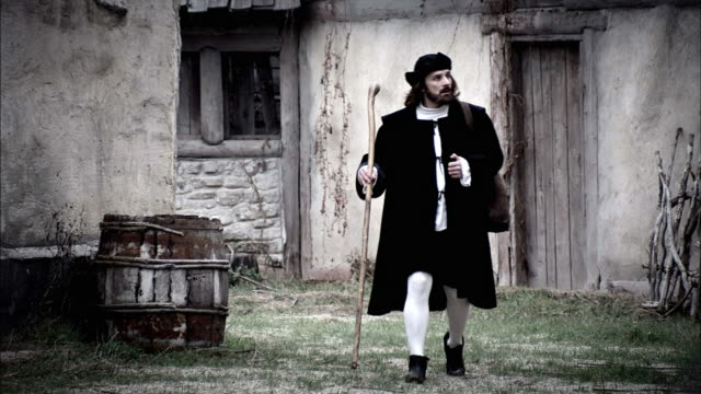 a robed man walks through an abandoned village. - reenactment stock videos & royalty-free footage