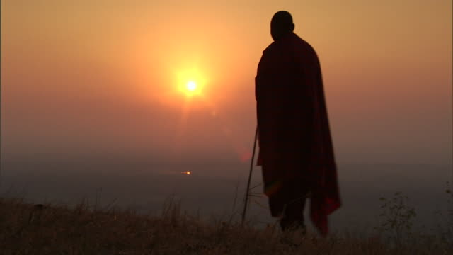 a robed masai man stands on a grassy hilltop and gazes across the golden horizon. - feierliche veranstaltung stock-videos und b-roll-filmmaterial